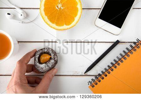 Hand holding chocolate cookie white wood table top carrot juice earphones slice of orange smart phone orange notebook black pencil around