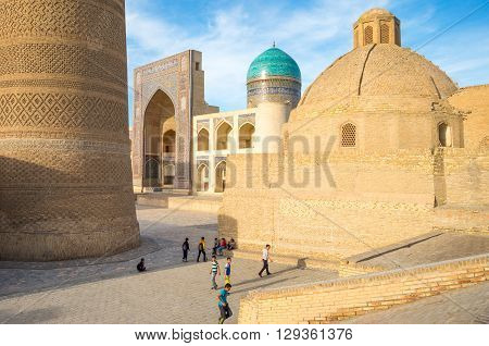 Buckara Uzbekistan - Aprilr 16 2014: Local boys playing under the Kalon minaret with the Mir-i-Arab madrassah in the background