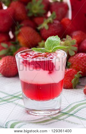 Pink coloured strawberry dessert in shot glass decorated with mint leaves on green white tablecloth several strawberries at background