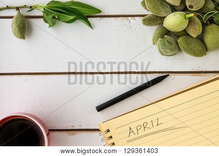 Flat lay view of white wooden background red coffee cup black pencil yellow notebook writing april unripe almonds