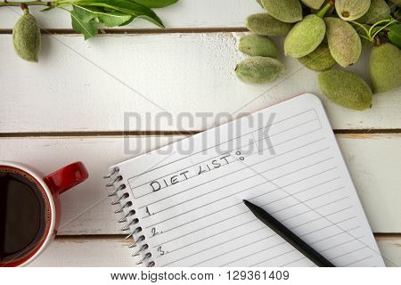 Flat lay of wooden white tray red coffee cup unripe almonds white notebook diet list written on white sheet