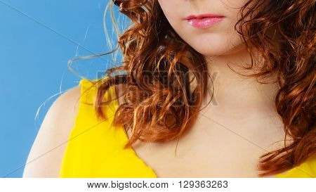 Closeup part of woman face female lips and glossy curly red hair girl on blue background
