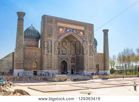 Samarkand Uzbekistan - April 18 2014: People around the Sher Dor madrassah in Registan square