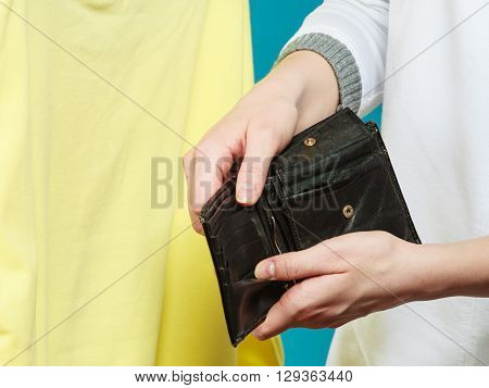 Broke human hands holding empty wallet purse. Lack of money for fashion clothes. Crisis and weak economy concept.