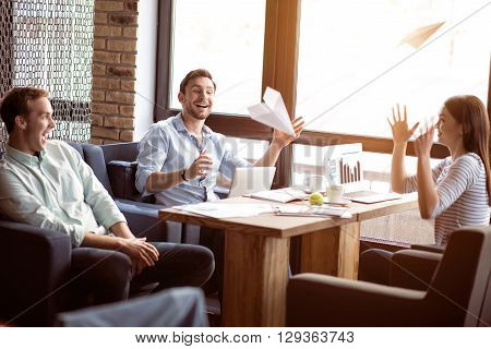 Like little children, Cheerful delighted joyful smiling colleagues sitting at the table and playing with paper planes while having fun