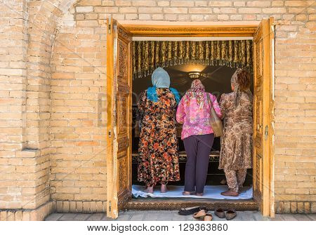 Samarkand Uzbekistan - April 18 2014: Local faithful in prayer in the St Daniel mausoleum