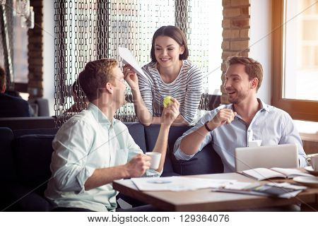 Lively atmosphere.  Delighted positive smiling colleagues sitting at the table and having a pleasant conversation while playing with paper planes