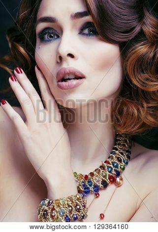 beauty rich woman with luxury jewellery looks like mature close up