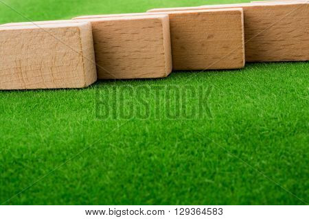 Brown color Wooden domino pieces on green gras