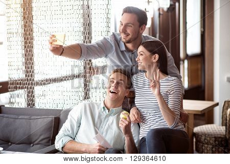 Say cheese. Overjoyed delighted smiling friends sitting on the couch and expressing gladness while making selfie