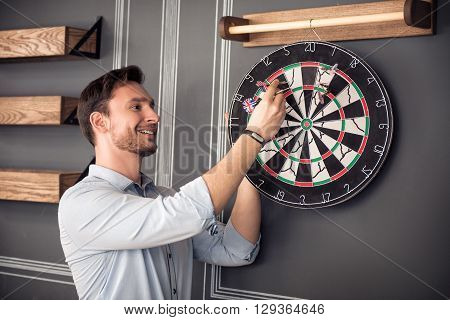 Relief negativity. Cheerful content handsome smiling man standing near the wall and expressing gladness while playing darts