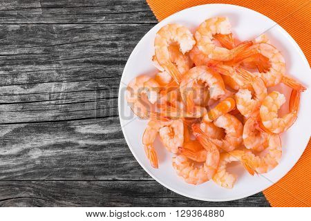boiled tails of king shrimps on a white dish on a table mat on an old rustic table blank space left studio lights view from above
