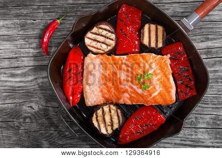 Delicious red fish salmon steak fillet on a iron grill pan with grilled bell pepper and grilled slices of aubergine close-up view from above