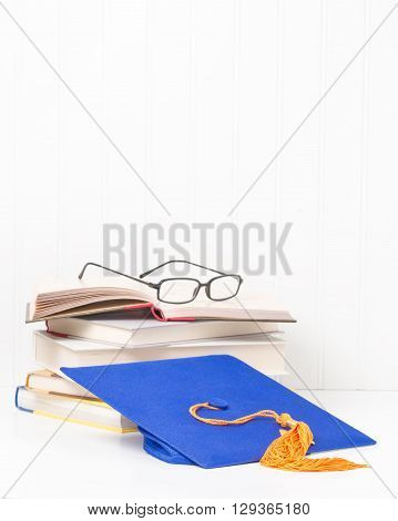 Blue graduation cap and a pile of textbooks with reading glasses.