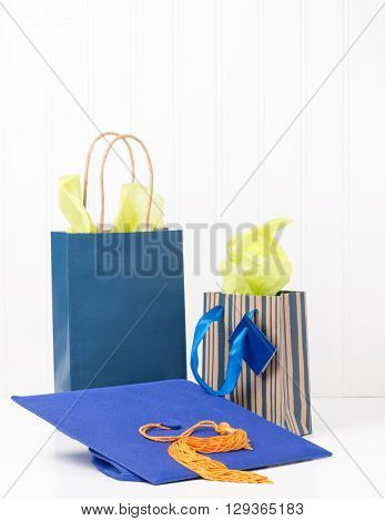 Blue graduation cap and two gift bags. Ample copy space available.