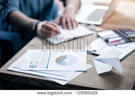 Professional worker. Selective focus of papers lying on the table  while pleasant man making notes in the background