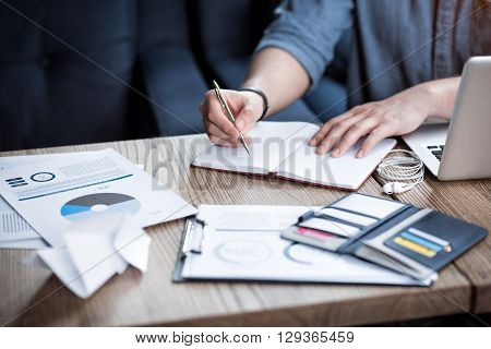 Do it in writing. Pleasant man sitting at the table and making notes while being involved in work