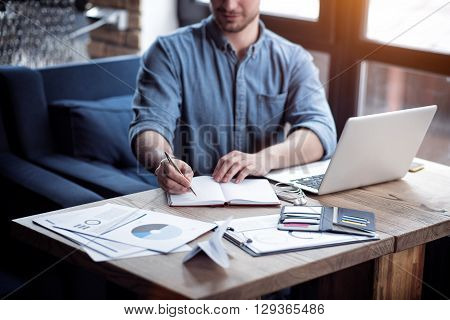 Busy worker. Handsome concentrated  man sitting at the table and making notes while being involved in work
