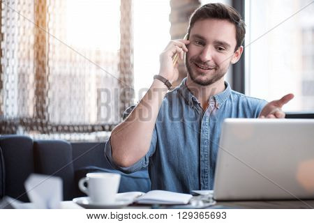 In touch with you. Cheerful handsome content smiling man sitting at the table and expressing gladness while talking on cell phone