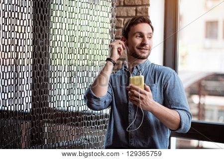 Involved in musical world. Pleasant delighted smiling man holding cell phone and listening to music while resting