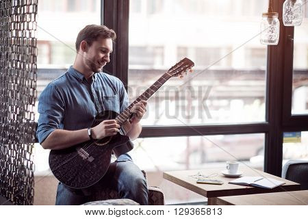 Like a real musician. Cheerful content smiling man leaning on the arm chair and playing the guitar while expressing gladness