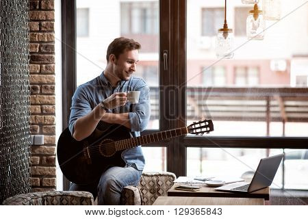 Involved in relaxation. Cheerful handsome delighted man leaning on the armchair and holding the guitar while drinking coffee
