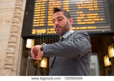 Commuter checking time in front of a timetable