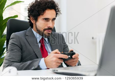 Businessman playing videogames in his office
