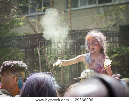 NEW YORK - APR 30 2016: An unidentified girl celebrates Holi Hai Festival of Colors with colorful powder on her face in Dag Hammerskjold Plaza hosted by NYC Bhangra in New York on April 30, 2016.