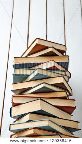 High stack of books on white wooden wall background