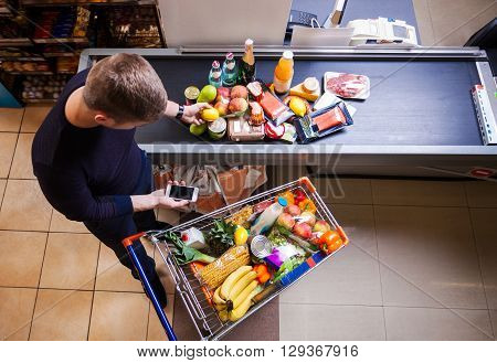 Young man before checkout in supermarket, view from above