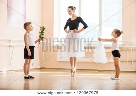 At ballet dancing class: young boy and girl giving flowers and veil to older student while she is dancing en pointe