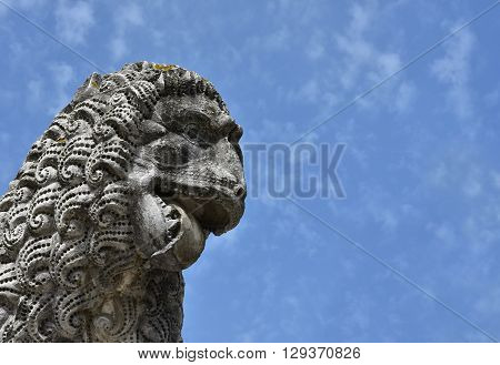 Ferocious lion head. Detail of an ancient lion statue in the Lucca medieval walls gardens