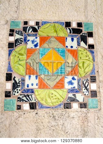 Close-up colorful Mexican ceramic tile design in a stone wall in an outdoor public area in San Antonio, Texas