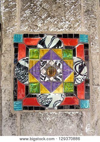 Close-up of colorful, geometric design ceramic tile inlaid in stone column in San Antonio, Texas public transportation area