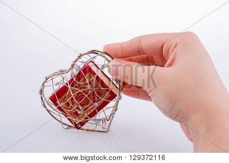The Holy Quran in a heart shaped cage on a white background