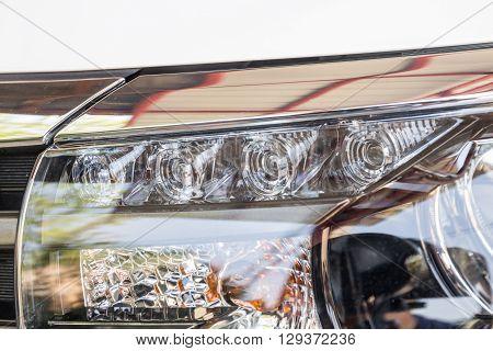 Closeup LED headlights daylight running of modern white car