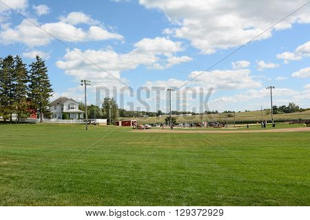 DYERSVILLE, IOWA - AUGUST 20, 2015: Field of Dreams movie set. Children and adults playing baseball on the diamond of the 1989 movie set.