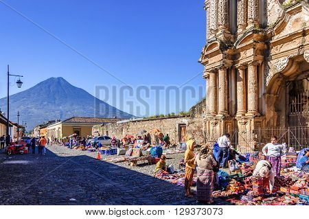 Antigua Guatemala - October 5 2014: Weekend Mayan textile market in cobblestone street outside El Carmen ruins with Agua volcano behind in colonial city & UNESCO World Heritage Site of Antigua.