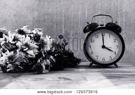 Alarm clock on wooden at home with flowers wither