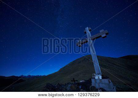 cross sign on the mountain peak pass at night