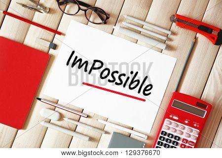 Word impossible transformed into possible on paper with school supplies