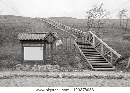 Billboard and wooden stairs hill and rocky road