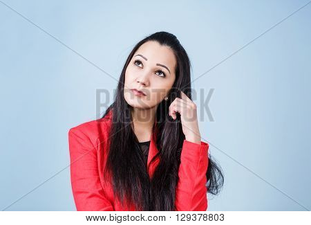Young thoughtful woman on the blue background