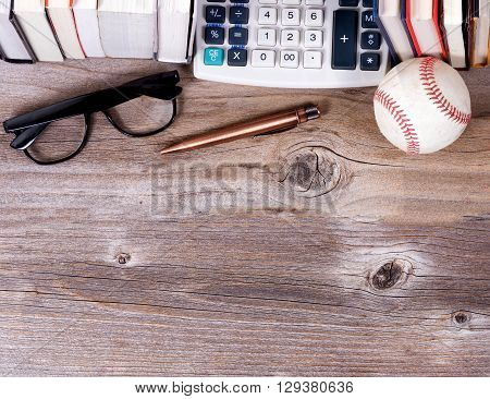 Overhead view of an old paper calculator books used baseball reading glasses and antique pen on rustic wooden boards.