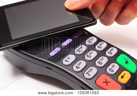 Hand of woman paying with NFC technology on mobile phone credit card reader payment terminal finance concept