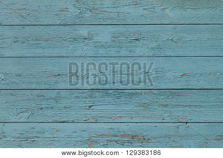 A weathered wall made with cyan painted wood panels