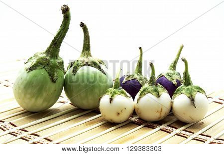 Two green brinal, three white eggplants and violet/purple eggplants on brown bamboo mat.
