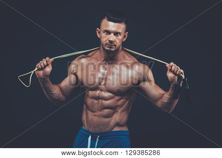 Muscular man skipping rope. Portrait of muscular young man exercising with jumping rope on black background. skipping  rope active  sport  fitness