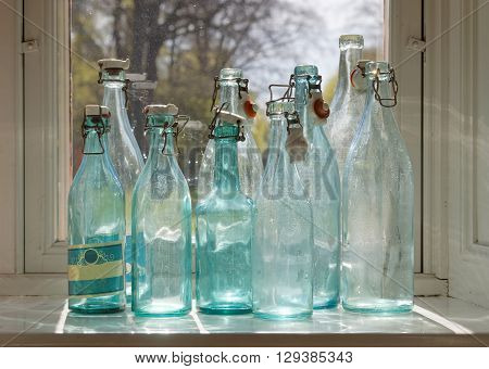 Group of back lit blue and transparent old fashioned empty glass bottles in a window. Trees in the background